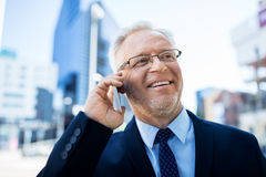 Smiling old businessman calling on smartphone stock images