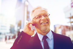 Smiling old businessman calling on smartphone stock photos
