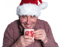 Smiling old casual man wearing a santa hat  is drinking a hot te Royalty Free Stock Photography