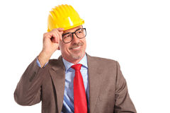 Smiling old construction engineer holding his helmet as a greeti Stock Photography