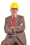 Smiling old construction engineer sitting with hands crossed Royalty Free Stock Image