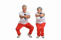 Smiling old couple. Amusing happy smiling old couple with dumbbells royalty free stock images