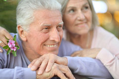 Smiling old couple with flowers Royalty Free Stock Photos