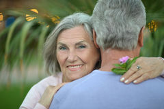 Smiling old couple with flowers Stock Photos