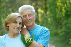 Smiling old couple with flowers Royalty Free Stock Images