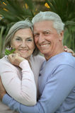 Smiling old couple with flowers Royalty Free Stock Image