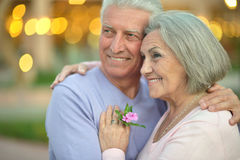 Smiling old couple with flowers Stock Images