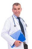 Smiling old doctor holding a blue notepad Royalty Free Stock Image