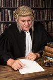 Smiling old judge. Old judge smiling in court wearing a vintage wig royalty free stock photo