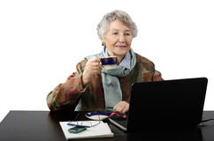 Smiling old lady drinking cup of coffee while talking in skype Stock Photos