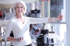 Smiling old lady exercising with dumbbells. Movement means life. Very happy senior slim lady is exercising with dumbbells at gym Stock Photo