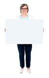 Smiling old lady holding blank whiteboard Royalty Free Stock Photos