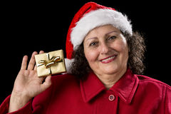 Smiling Old Lady Shows Golden Wrapped Christmas Gift. Happy female pensioner with red Santa Claus hat is showing a golden wrapped Christmas present in her right Royalty Free Stock Image