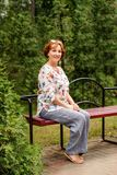 Smiling aged lady sits on a bench in the greenery parks in linen clothes stock images