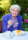 Smiling Old Lady Taking Snacks at the Garden Table Royalty Free Stock Image