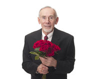 Smiling old man with bunch of red roses. Happy elderly man holding a beautiful bunch of red roses as a gift to someone he loves. He is elegantly dressed in a Stock Images