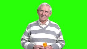 Smiling old man with can pills. Grandpa holding can with painkillers in green background stock footage