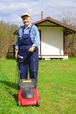 Smiling old man cutting grass using lawn mower Royalty Free Stock Photography