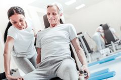 Smiling old man exercising and a trainer helping him. Therapist. Gleeful determined old grey-haired men smiling and exercising on a training device while a dark Royalty Free Stock Images
