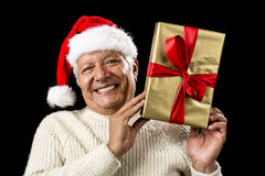 Smiling Old Man With Golden Gift Isolated On Black. Aged man brimming over with a hearty smile, while lifting up a foot-long golden gift suspended between the Stock Photography
