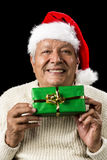 Smiling Old Man Handing Over A Wrapped Green Gift. Male senior with warm smile and red Father Christmas cap. He is holding a wrapped, oblong, green present above Stock Image