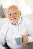 Smiling old man having coffee. Portrait of smiling old man having coffee, looking happy Royalty Free Stock Photography