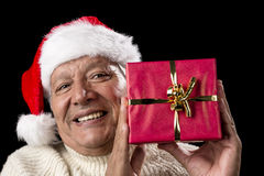 Smiling Old Man With Red Wrapped Christmas Gift. Joyful male senior is presenting a red wrapped Christmas present. He is wearing a Santa Claus hat and a warm Royalty Free Stock Photo