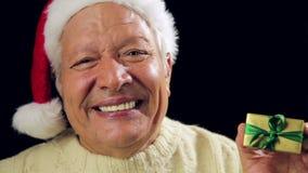 Smiling Old Man With Santa Cap Points At Xmas Gift stock footage