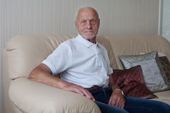 Smiling old man sitting on sofa Stock Images