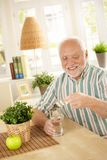 Smiling old man taking medication. With water, holding bubble package, sitting at home Stock Image