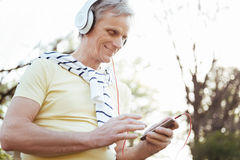 Smiling old man using electronic gadgets outdoors stock photos