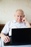Smiling old man working on a computer Stock Image