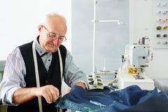 Smiling Old Man Working in Tailoring Stock Image