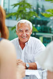 Smiling old manager sitting on table Stock Images