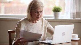Smiling old mature lady paying bills online on laptop