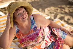 Smiling old woman at beach on sunbed Royalty Free Stock Photography
