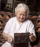 Smiling old woman with casket Stock Image
