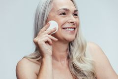Woman cleansing her face stock photos