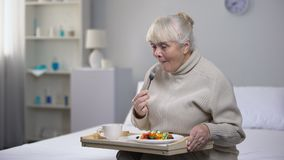 Smiling old woman eating dinner in nursing home, social security for aged people