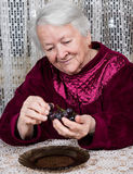 Smiling old woman eating grapes Stock Photo