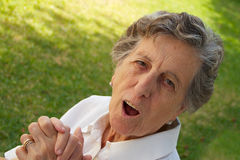 A smiling old woman is expressing her feeling of being astonishe. A happy smiling old woman between 70 and 80 years old is keeping two hands together sitting in Royalty Free Stock Photo