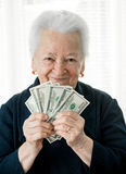 Smiling old woman holding money in hands Stock Photo
