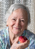 Smiling old woman holding red apple Stock Image