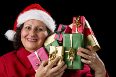 Smiling Old Woman is Holding Seven Wrapped Gifts. Joyful senior woman is holding up a bunch of wrapped Christmas presents like a violin. Santa Claus cap and red Royalty Free Stock Photos