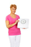 Smiling old woman holding weight scale Royalty Free Stock Photo