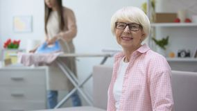 Smiling old woman looking at camera, granddaughter ironing clothes on background. Stock footage stock video footage