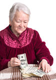 Smiling old woman with money on the table Stock Photography