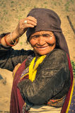 Smiling old woman in Nepal. Dolpo, Nepal - circa May 2012: Old native woman with wrinkled face and brown headcloth holds her hand on head in Dolpo, Nepal Stock Image