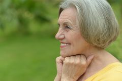 Smiling old woman. Nice smiling old woman on the green leaves background Royalty Free Stock Images