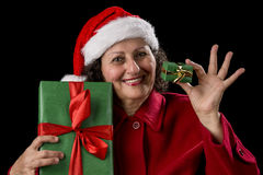 Smiling Old Woman Offering a Small and a Big Gift. Aged lady is showing two wrapped Xmas presents, one small, one bigger. She is wearing a red coat and a Santa Royalty Free Stock Photos
